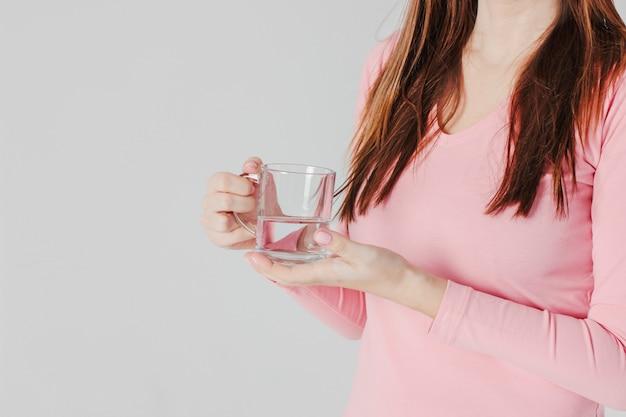 グレーの背中に女性の手の中の清潔な水の半分のガラスのカップ