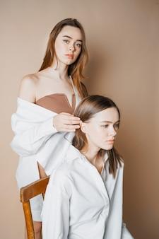 Модные модели двух сестер-близняшек красивых обнаженных девушек