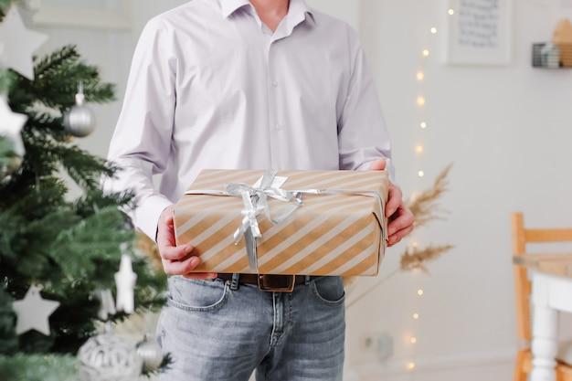 Молодой человек, держащий в руках рождественский подарок дома