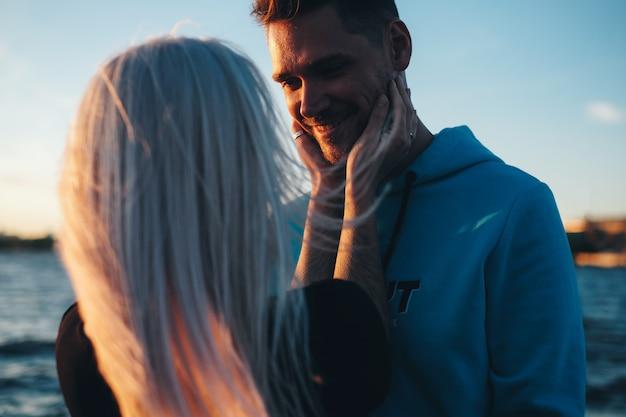 Девушка держит лицо молодого человека, влюбленная пара на пирсе