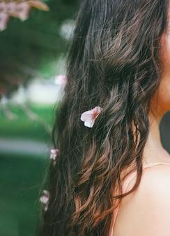 ピンクの花と暗い巻き毛の長い髪のスタイルを持つ若い女の少女