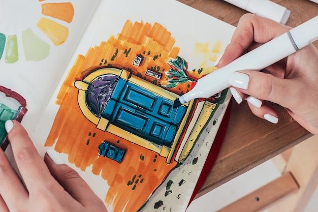 スケッチブックのマーカーで明るいドアのスケッチを描く