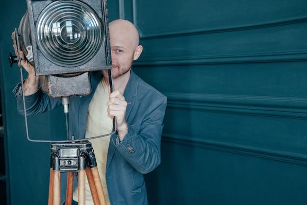古い照明器具、ビデオライトの周り探しているスーツのひげを持つ魅力的な大人のハゲ男
