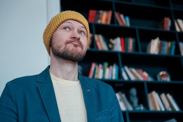 黄色の帽子で魅力的な大人のひげを生やした男のヒップスターを検索し、本の壁にこっそり微笑む