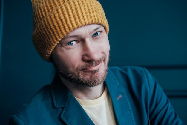 カメラに探していると青い壁に笑顔黄色い帽子で魅力的な大人のひげを生やした男のヒップスター