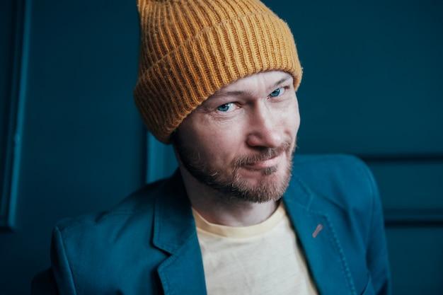 カメラに探していると笑顔の黄色い帽子で魅力的な大人のひげを生やした男ヒップスター
