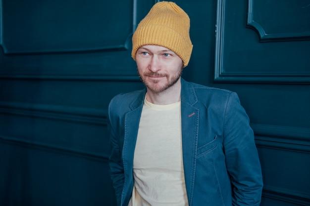 黄色の帽子で魅力的な大人のひげを生やした男流行に敏感な青い壁の背景にカメラを見てください。