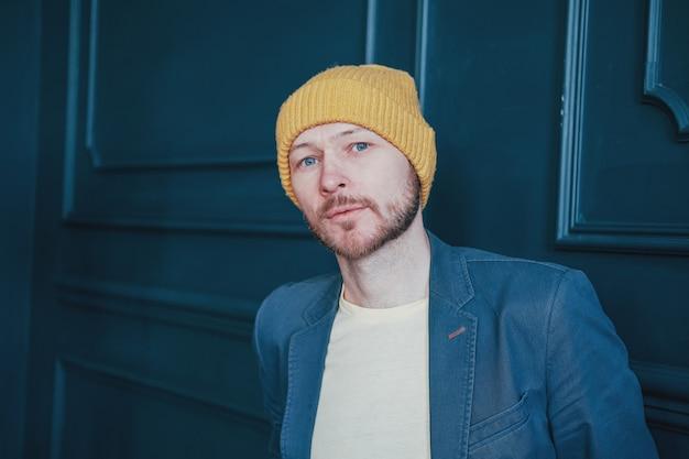 カメラを疑って見ている黄色の帽子で魅力的な大人のひげを生やした男ヒップスター