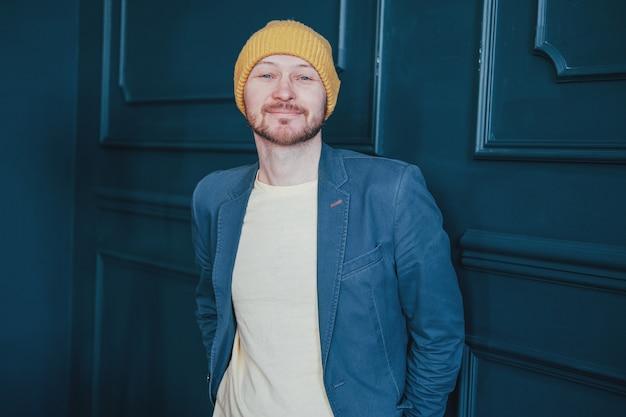 青い壁にカメラを見て優しい黄色の帽子で魅力的な大人のひげを生やした男ヒップスター