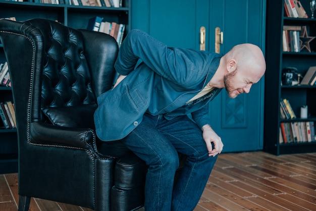 Привлекательный лысый бородатый мужчина держится за спину, пытаясь встать с кожаного кресла