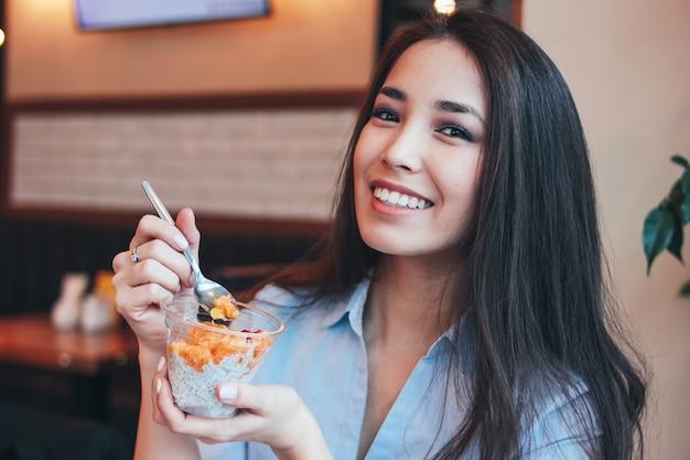 美しい魅力的なブルネットの笑顔アジアの女の子はカフェでチアプリンと朝食を持っています