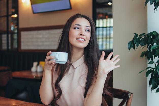 アジアの女の子を笑顔の美しい魅力的なブルネットの長い髪はカフェでコーヒーと朝食を持っているし、友達に手を振って