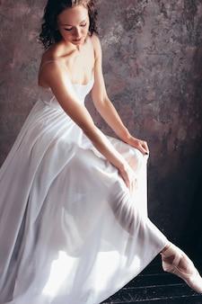 美しい薄い飛んで白いドレスのバレエダンサーバレリーナは暗いロフトスタジオでポーズをとっています。