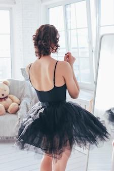 鏡の前で黒いドレスのバレエダンサーバレリーナの率直な肖像画