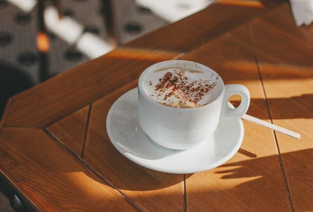 泡とシナモンのカプチーノコーヒーカップ木製テーブルの上。