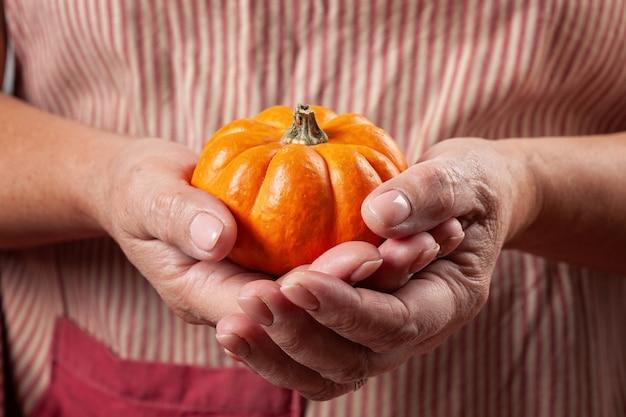 カボチャを保持している女性の手。