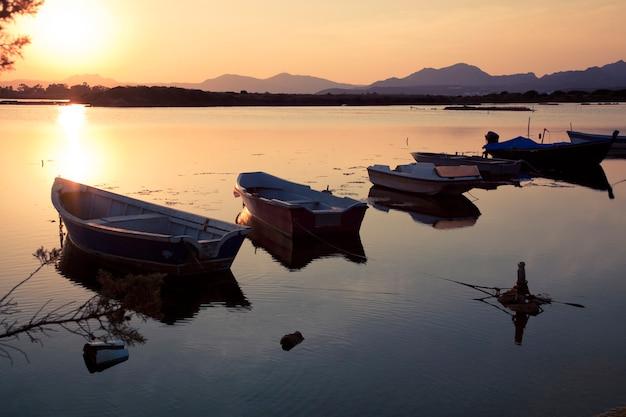 夕暮れ時の湖で漁船
