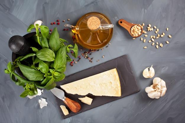 パルメザンチーズ、オリーブオイル、バジル、ニンニク、松の実-ペスト料理のレシピの新鮮な食材。イタリアのキッチンコンセプト