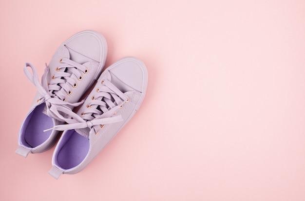 ファッションのブログや雑誌のコンセプト。パステルピンクの背景の上のピンクの女性のスニーカー。ショッピング、販売、ファッションブログのフラットレイアウト、トップビューの最小限の画像