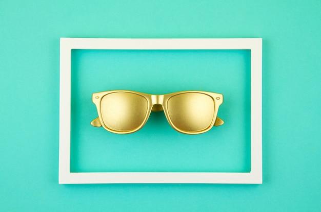 パステルカラーのターコイズブルーの背景の上の黄金のトレンディなサングラスのトップビュー