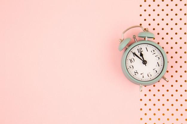 パステル調の背景にビンテージの目覚まし時計でフラットレイアウト