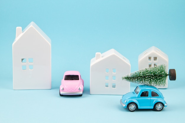 屋根の上のクリスマスツリーを運ぶ小さなおもちゃの車。季節の休日、グリーティングカード
