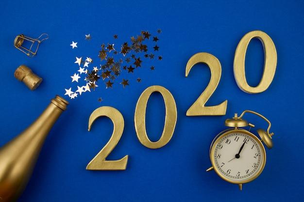 トップビューの数字、シャンパン、グラス、目覚まし時計、紙吹雪のゴールデンボトル。パーティー、新年、お祝い