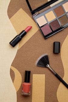 Губная помада, тени для век, кисточка для макияжа и накладные ресницы. визажист, салон красоты, блог красоты
