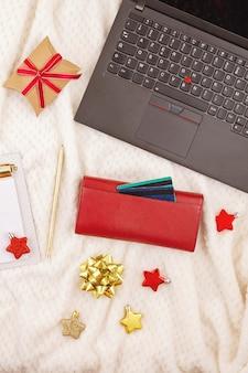 ラップトップ、クレジットカード、財布、クリスマスの装飾。オンラインクリスマスショッピング、ギフトの購入