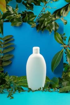 Фон с зелеными листьями и растений и бутылка косметики. концепция естественного ухода за кожей
