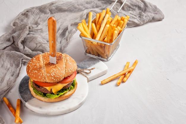 チーズ、トマト、フライドポテトのサラダと新鮮なおいしいハンバーガー