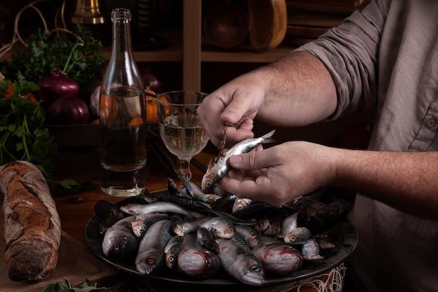 Рыбак чистит свежую рыбу