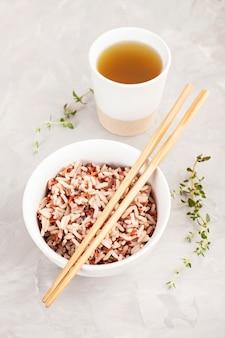 セラミックボウルと箸と緑茶の盛り合わせマルチカラーワイルドライス。黒、茶色、白ご飯。