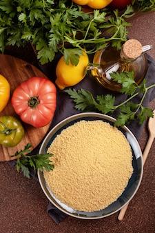 Свежие ингредиенты для салата табуле: кус-кус, помидоры, лимон, петрушка, мята, оливковое масло, сладкий перец. здоровая вегетарианская концепция халяльной пищи
