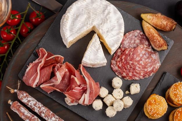Закуски столовые с разными закусками, сырами, колбасами, закусками и вином. мини-гамбургеры, колбаса, ветчина, тапас, оливки, сыр и багет на серой бетонной поверхности. вид сверху, плоская планировка