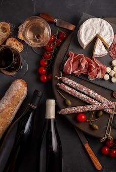 前菜には、さまざまな前菜、チーズ、炭火焼き、スナック、ワインが含まれています。ミニハンバーガー、ソーセージ、ハム、タパス、オリーブ、チーズ、バゲットを灰色のコンクリート表面に。平面図、平置き