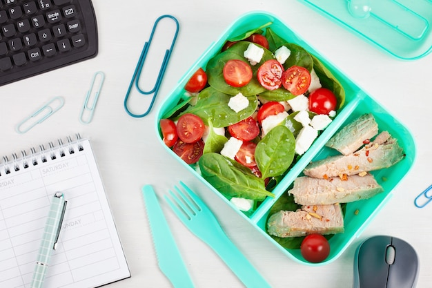 新鮮なサラダとマグロの入ったランチボックスを、事務用品を置いたオフィスデスクの上に置きます。