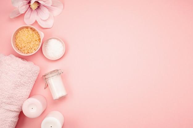 ピンクの背景の上の女性の美しさとスパ製品、ツール、化粧品