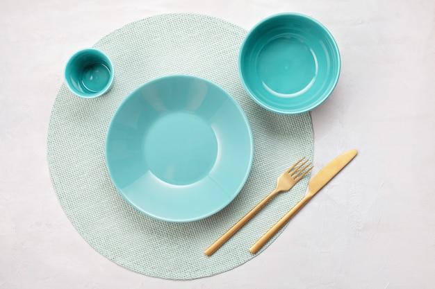 С пустой тарелкой, бокалом, миской, вилкой и ножом.