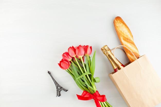 赤いチューリップのブーケとショッピングバッグにフランスのバゲット
