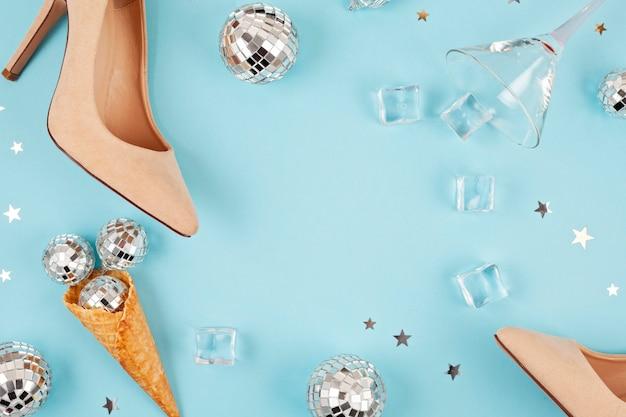 女性の靴、ディスコボール、アイスキューブ、カクテルグラス、紙吹雪とフラットレイアウト。