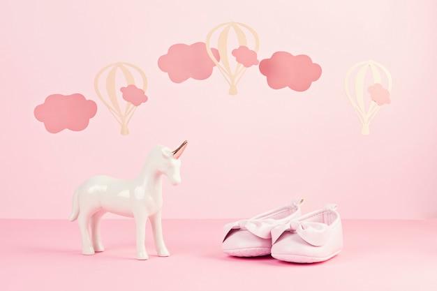 Девочка в милых розовых туфлях и единороге на розовом пастельном фоне