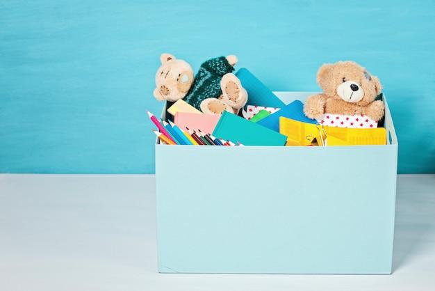 学用品やおもちゃを持つ子供たちへの寄付のある箱