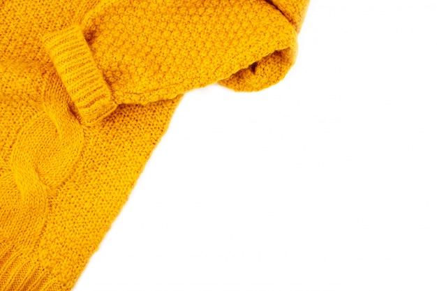 Текстура оранжевый шерстяной вязаный свитер на белом фоне с копией пространства. комфортная теплая одежда для концепции холодной погоды