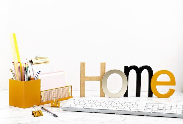ポットとオフィス用品、コンピューターのキーボードとマウスの花を持つホームオフィスコンセプト