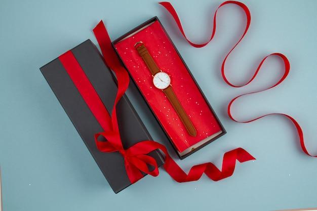 Женские наручные часы в черной подарочной коробке с красной лентой