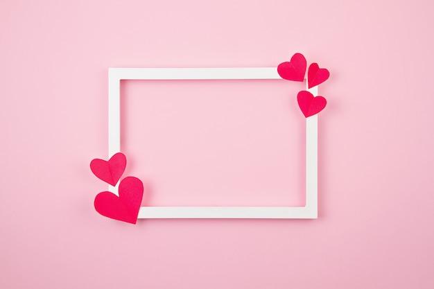 Бумажные сердца и белая рамка на розовом фоне пастельных.