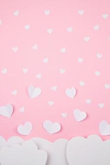 Бумажные сердца и облака на розовом фоне.