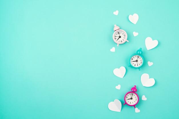Белые бумажные сердца, будильники и облака на бирюзовом фоне. день святого валентина, день матери, поздравительные открытки на день рождения, приглашение, концепция праздника