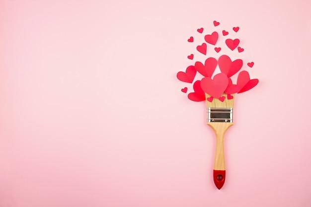 Бумажные сердца и кисть на розовом фоне пастель.